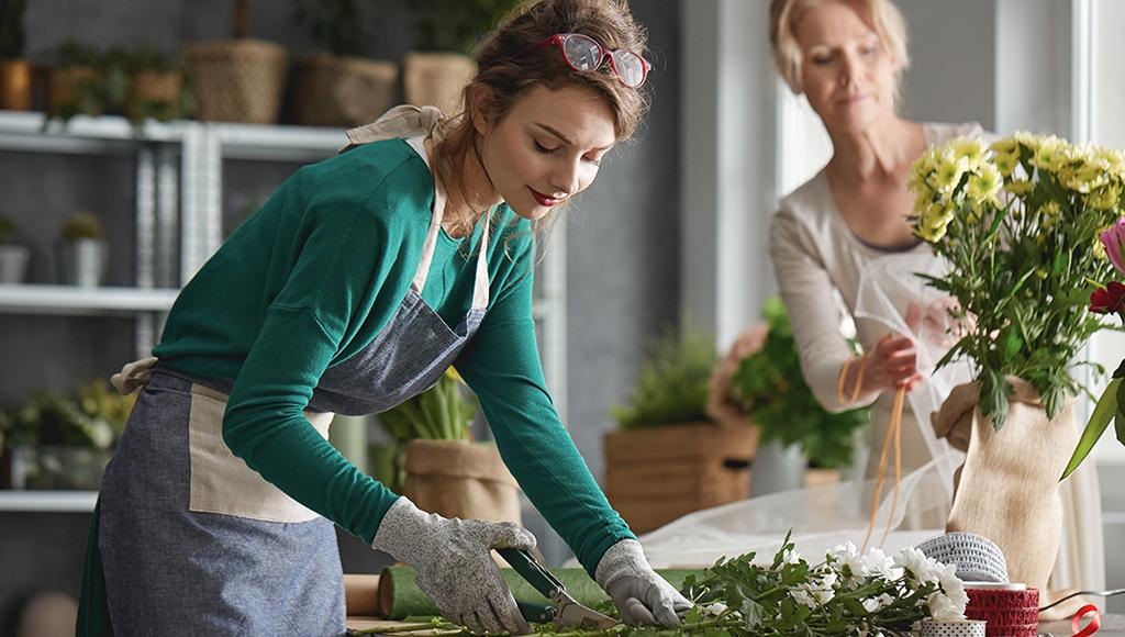 Eine Floristin schneidet Blumen, im Hintergrund bindet eine weitere Mitarbeiterin einen Strauß