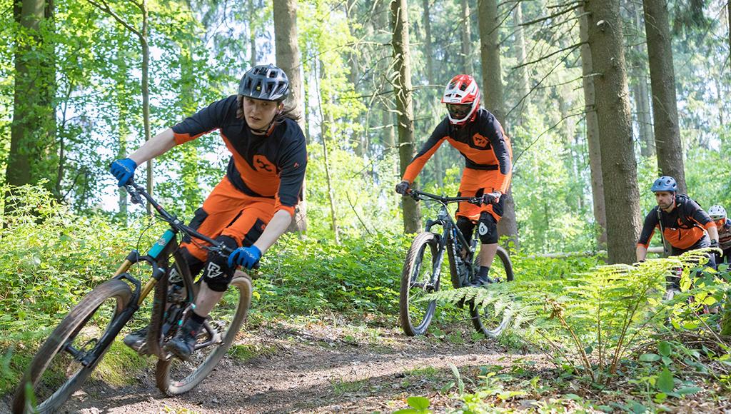 Drei Fahrradfahrer fahren eine buckelige Piste im Wald