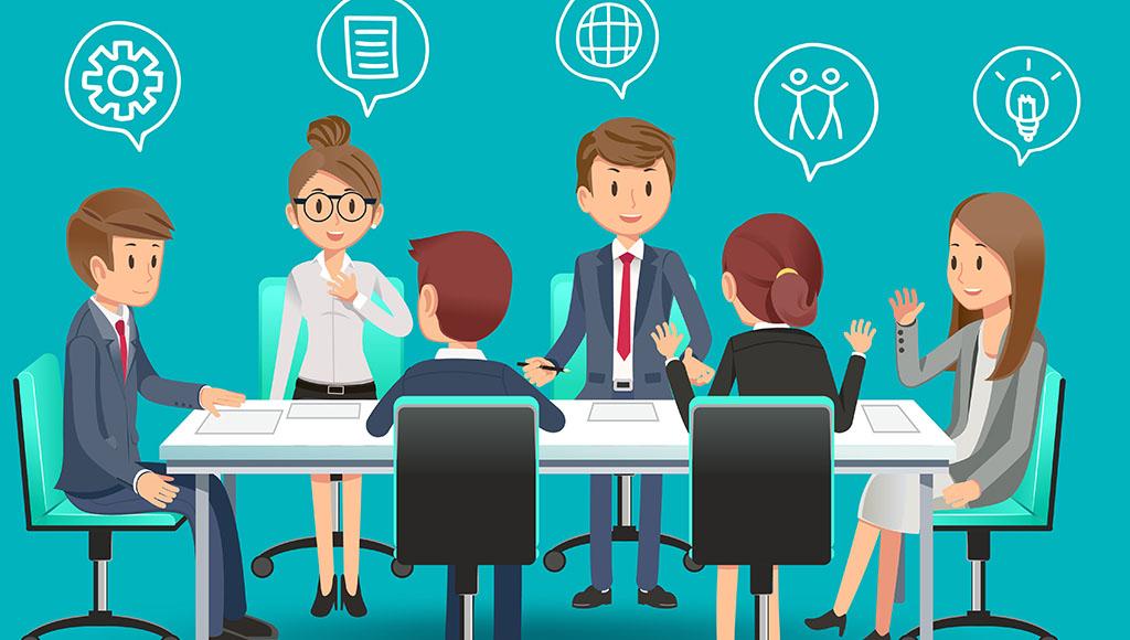 An einem Meeting-Tisch sitzen mehrere Beschäftigte und unterhalten sich angeregt