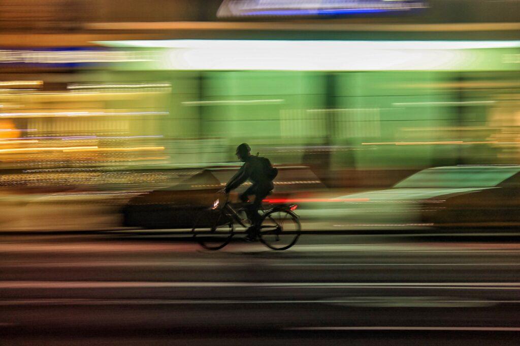 Stadtverkehr, ein Fahrradfahrer fährt an parkenden Autos vorbei