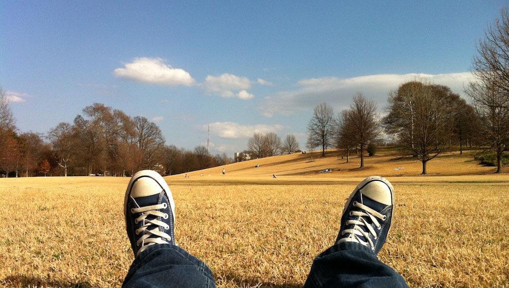 Zu sehen ist die Perspektive eines liegenden Menschen: seine Sneakers vor einer weiten Parklandschaft