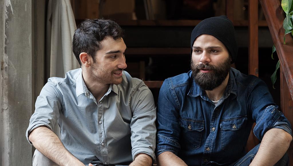 Zwei Männer sitzen nebeneinander und unterhalten sich kollegial.