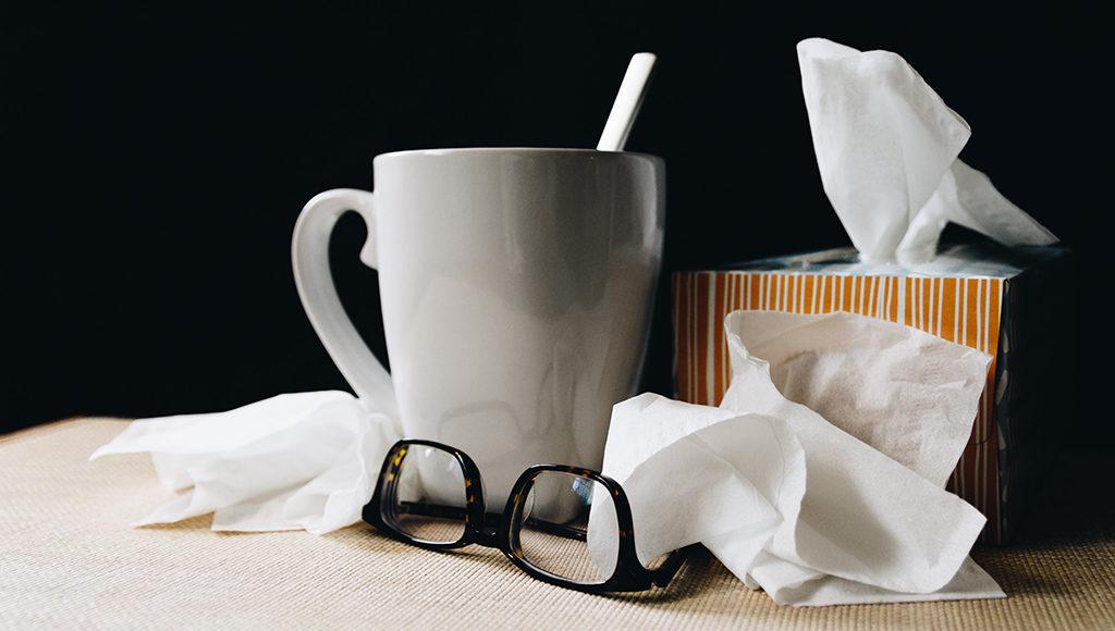 Auf dem Bild sind eine Tasse Tee und viele benutze Taschentücher zu sehen