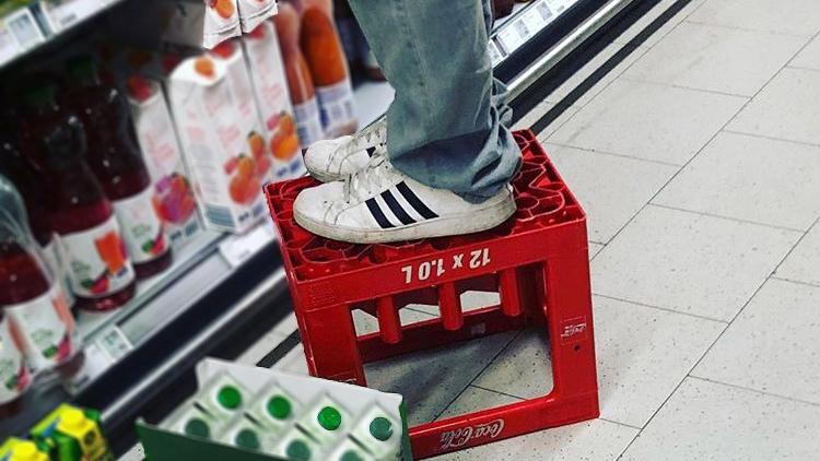 Ein Mitarbeiter steht im Supermarkt auf einer umgedrehten Getränkekiste.