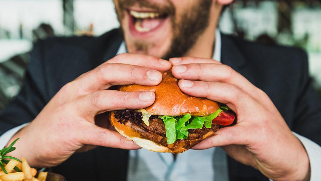 Zu sehen ist ein Hamburger im Vordergrund und ein lachender Mann im Hintergrund