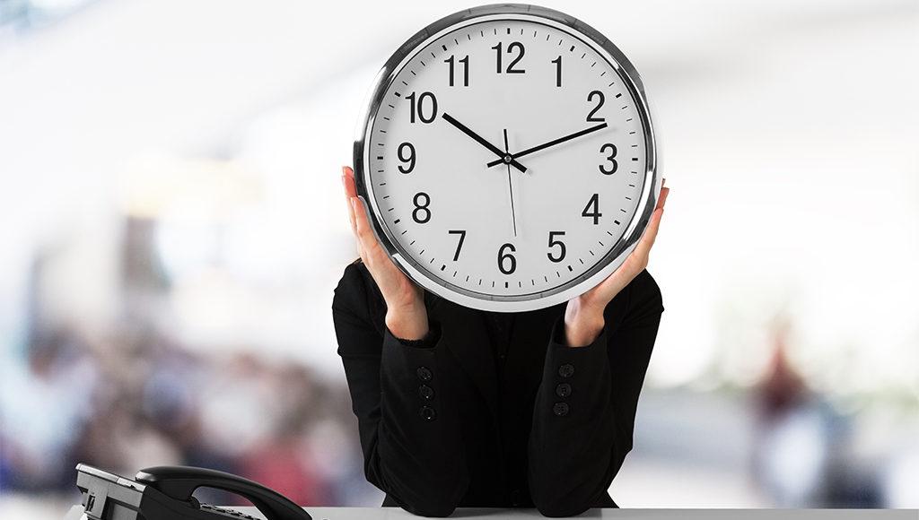 Eine Person hält sich eine große Uhr vor das Gesicht.