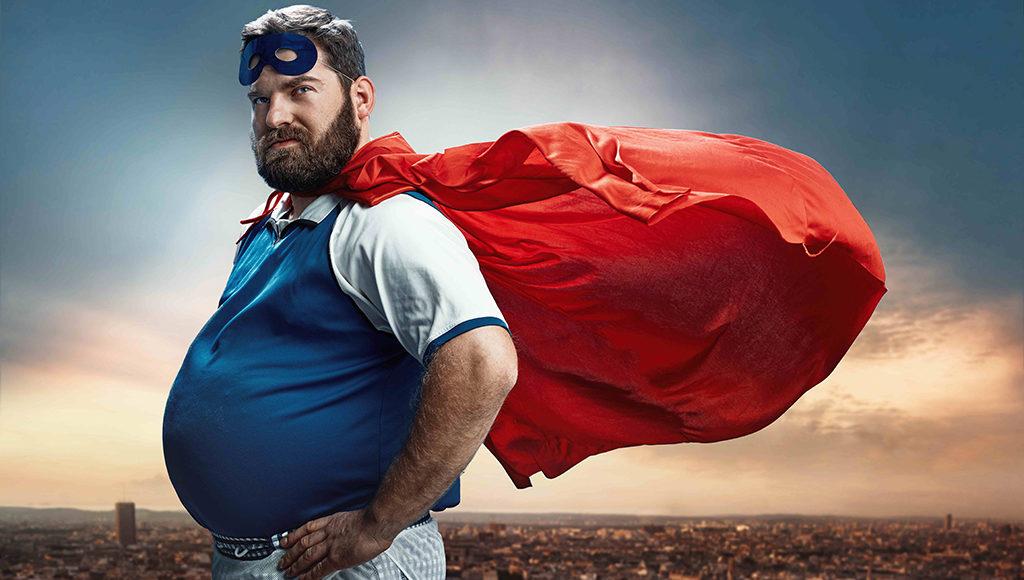 Ein mittelalter Mann blickt im Superhelden-Kostüm in die Kamera