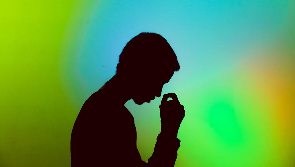 Zu sehen ist die Silhoeutte eines Mannes vor grünem Hintergrund.