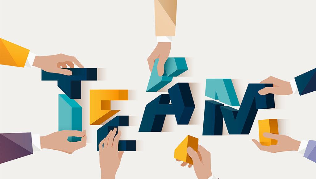 """Zu sehen sind vier Handpaare, die gemeinsam die Buchstaben zum Wort """"Team"""" legen."""