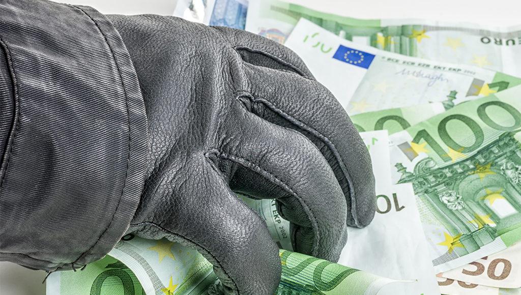 Zu sehen ist eine behandschuhte Hand, die nach vielen 100-Euro-Scheinen greift