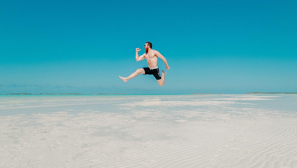 Ein Mann springt mit voller Freude am Strand in die Luft.