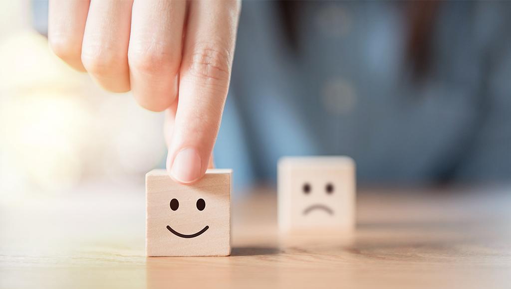 2 Würfel mit je einem positiven und negativen Smilie. Der positive Smiley wird in den Vordergrund gerückt.