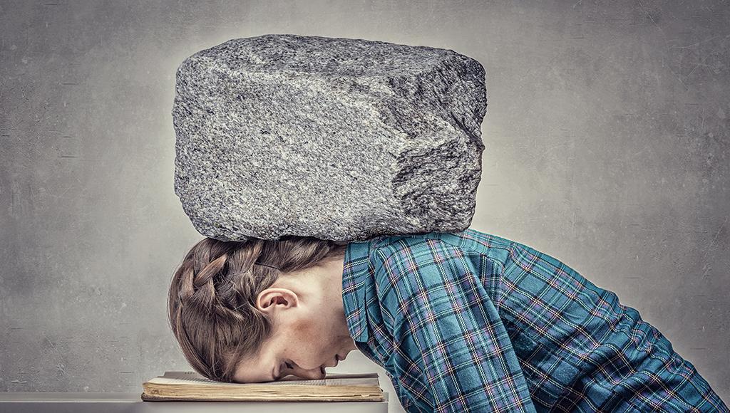 Eine junge Frau ist vorn über gebeugt und hat die Stirn auf einer Akte, die auf einem Tisch liegt. Ein Stein liegt ihr schwer im Nacken.