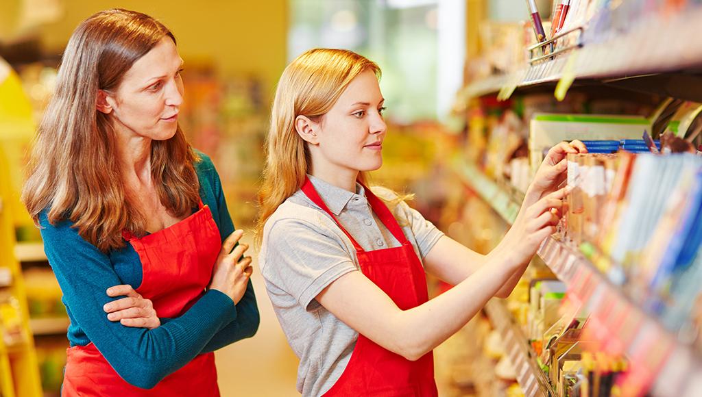 Azubi im Supermarkt räumt unter der Aufsicht von einer Verkäuferin ein Regal ein.