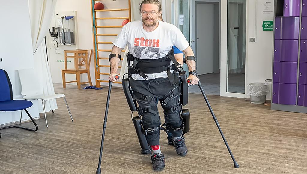 Marcus Kriegel macht mithilfe eines Exoskeletts und zweier Krücken Gehübungen in einem Reha-Raum eines Klinikums.