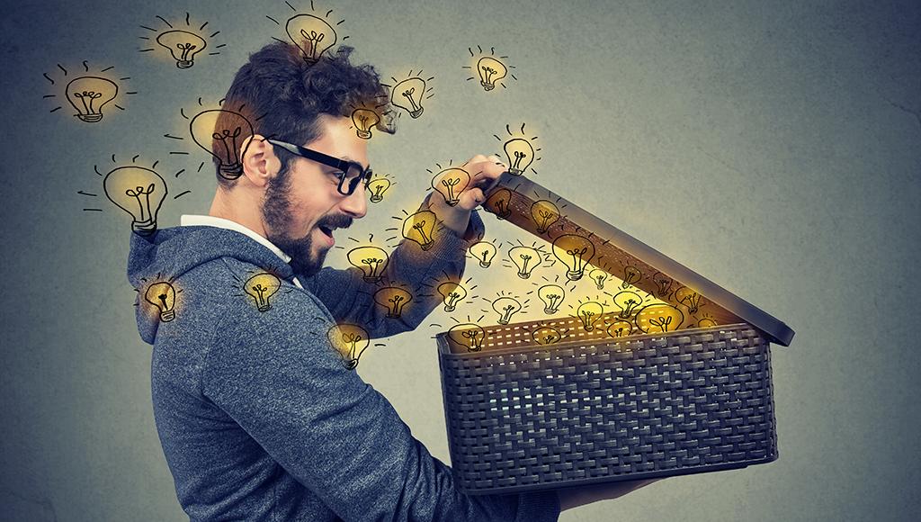 Ein Mann öffnet eine Kiste und wird von vielen Glühbrinen erleuchtet.