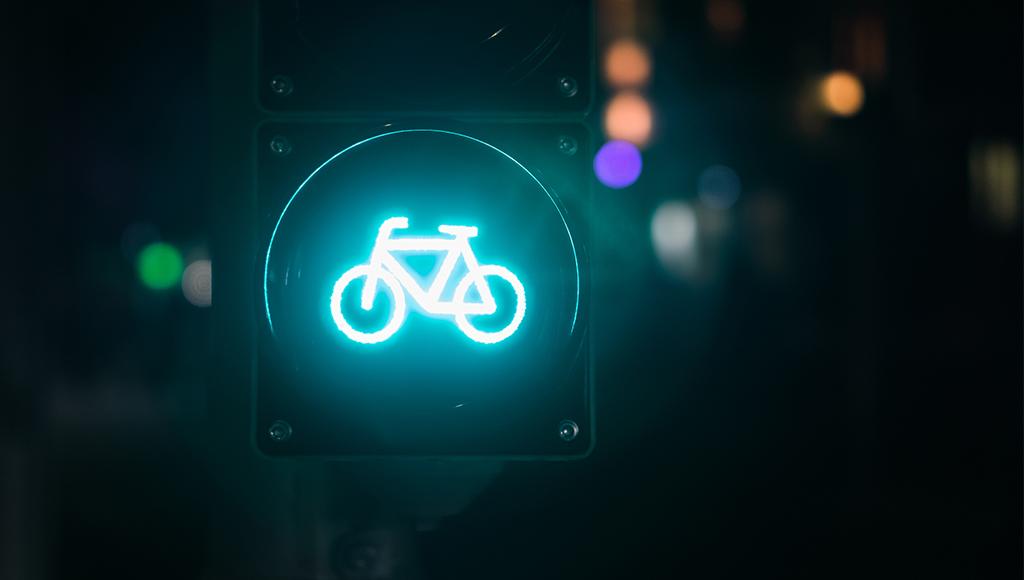 Zu sehen ist eine leuchtend grüne Fahrradampel in der Dunkelheit