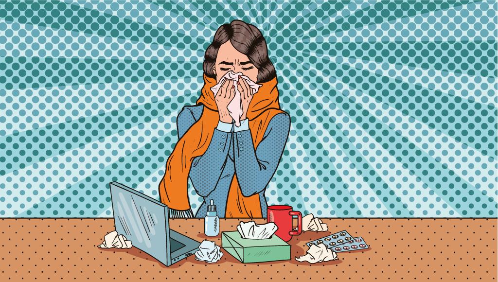Eine Mitarbeiterin sitzt erkältet am Arbeitsplatz. Sie putzt sich die Nase. Überall liegen benutzte Taschentücher herum.