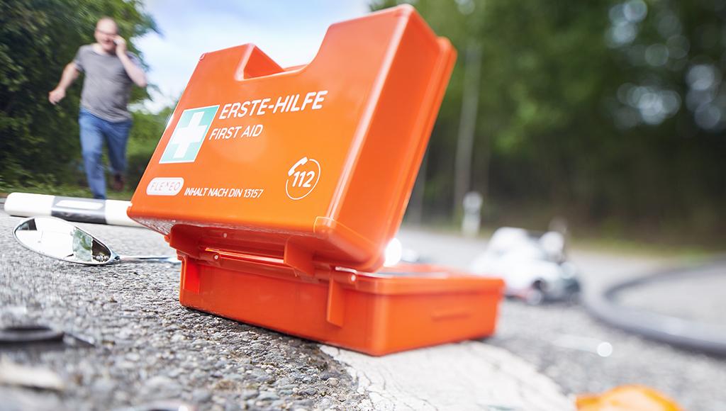 Großaufnahme eines orangefarbenen Erste Hilfe Koffers, der an einem Unfallort liegt. Im Hintergrund rennt ein Mann.