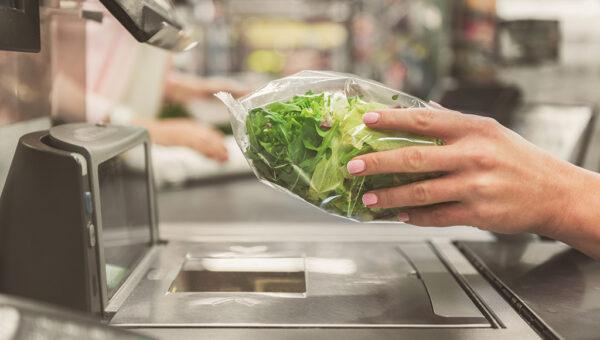Hände führen einen in Plastik eingepackten Salat über eine Scannerkasse.