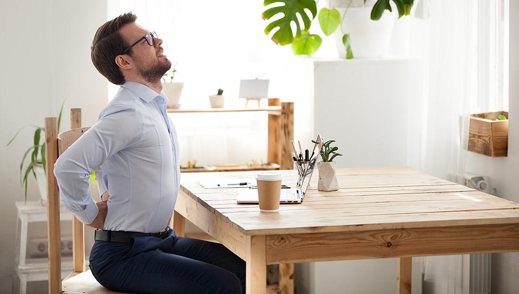 Mann auf Holzstuhl an Küchentisch mit Laptop. Mann krümmt sich mit Rückenschmerzen.