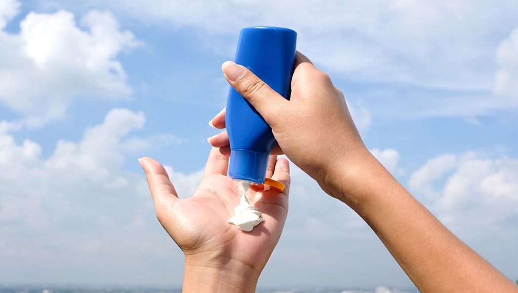 Rechte Hand drückt auf Sonnencreme-Flasche. Die Creme befindet sich in der linken Handinnenfläche.