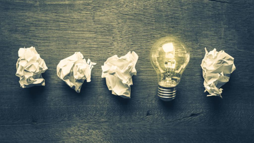 4 zerknüllte Zettel und eine Glühbirne. Ein Licht geht auf.