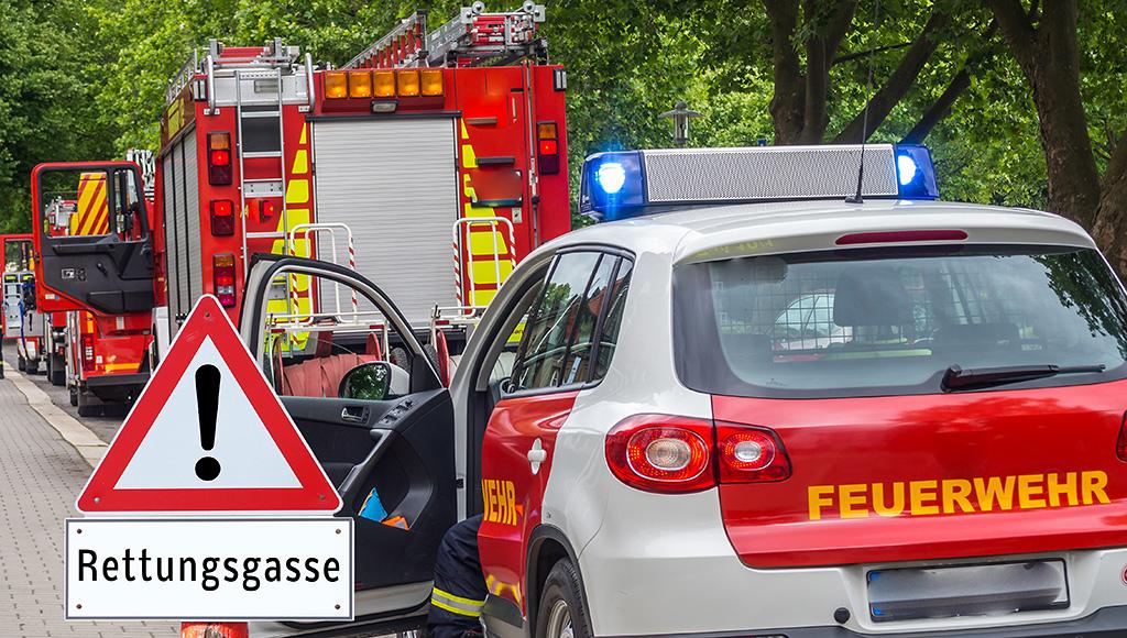 Es werden Einsatzfahrzeuge der Feuerwehr gezeigt. Hinweis mit Text-Schild Rettungsgasse.