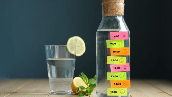 Ein Glas. Eine Wasserflasche mit Post-its und Uhrzeiten.