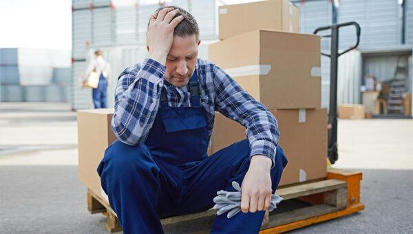 Mann sitzt niedergeschlagen am Arbeitsplatz und hält die Hand am Kopf.