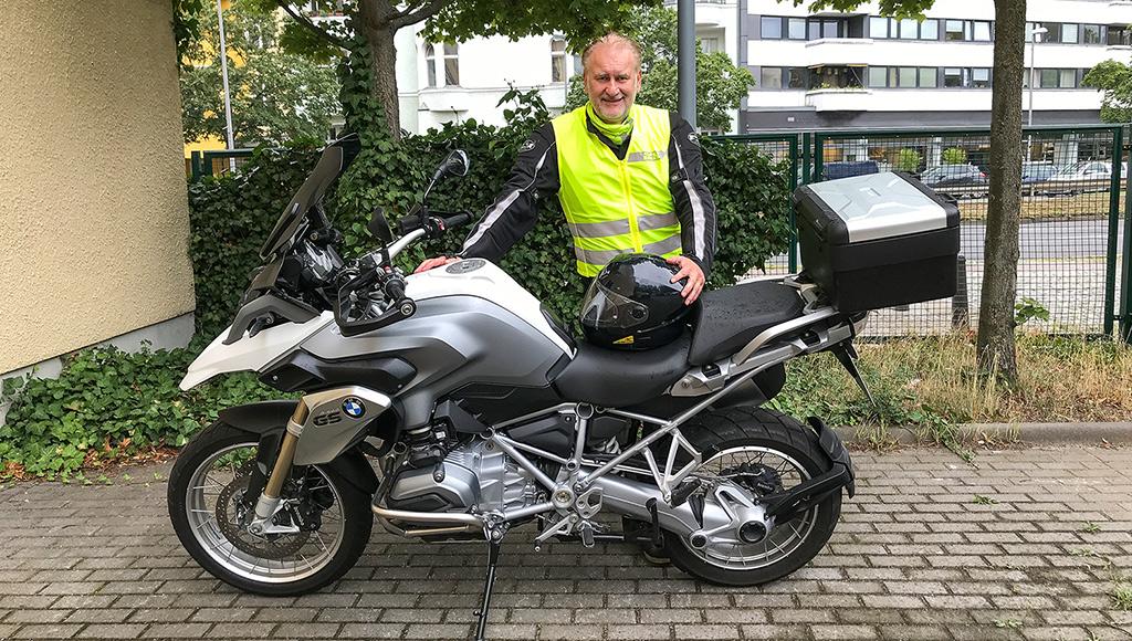 Bernd Wittwer steht hinter seinem Motorrad (BMW). Er trägt Schutzkleidung und eine gelbe Warnweste.