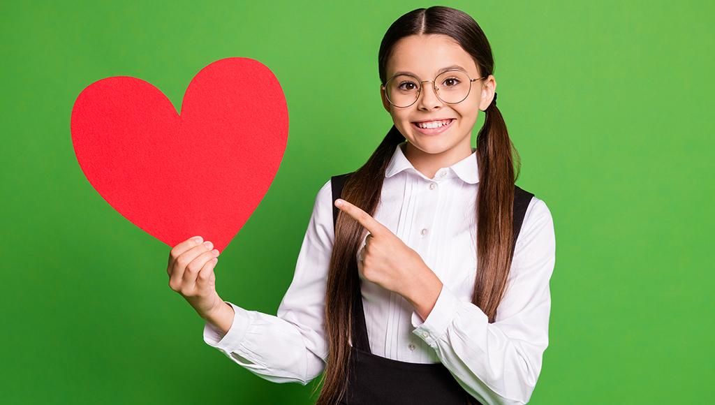 Mädchen hält Herz in der Hand