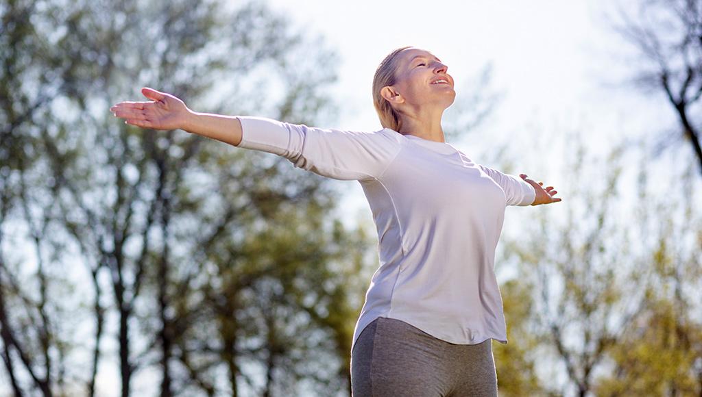 Frau streckt die Arme aus. Sie genießt die frische Frühjahrsluft.