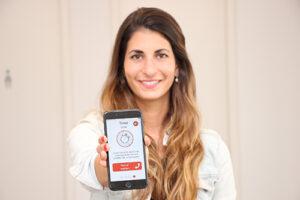 Frau hält Handy und zeigt die App FAST.