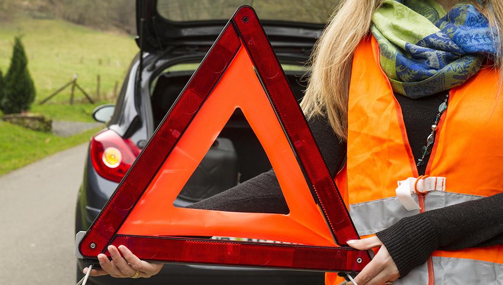 Eine Frau in Warnweste holt ein Warndreieck aus ihrem Kofferraum