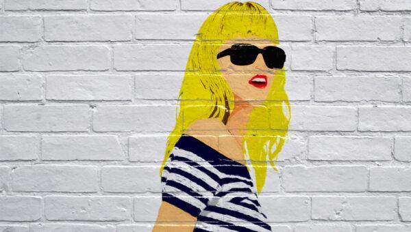 Graffiti von einer blonden Frau mit Sonnenbrille auf einer weißen Wand